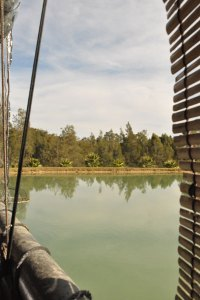 Photo looking across the bamboo blinds out to the lake and shoreline> Leaves & Fishes restaurant