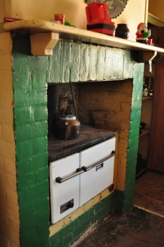 An old kooka wood oven, in working condition, with green brick surrounds and mantlepiece